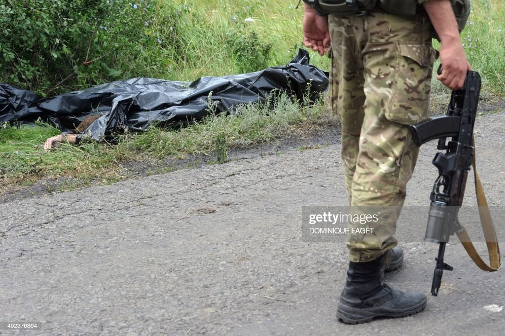 An armed pro-Russia militant walks by a dead body near the site of the crash of a Malaysia Airlines plane carrying 298 people from Amsterdam to Kuala Lumpur in Grabove, in rebel-held east Ukraine, on July 19, 2014. Ukraine and pro-Russian insurgents agreed on July 19 to set up a security zone around the crash site of a Malaysian jet whose downing in the rebel-held east has drawn global condemnation of the Kremlin. Outraged world leaders have demanded Russia's immediate cooperation in a prompt and independent probe into the shooting down on July 17 of flight MH17 with 298 people on board.