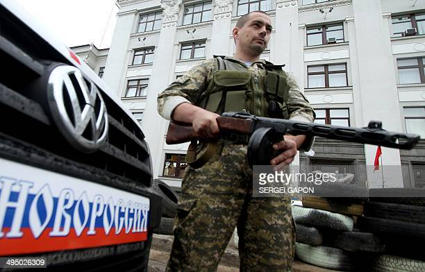 An armed proRussian militant guards a barricade outside the regional state building they seized in the eastern Ukrainian city of Lugansk on June 1...