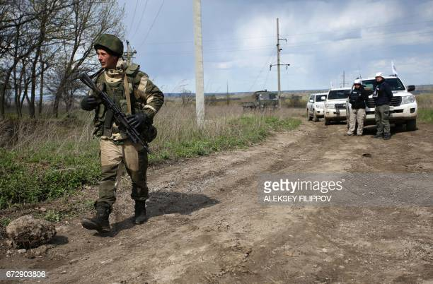 An armed proRussian separatist of the selfproclaimed Lugansk People's Republic walks past a convoy of the OSCE near village Pryshyb near Lugansk on...