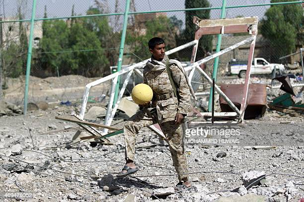 An armed Shiite Huthi rebel holds a ball on April 12 2015 at the compound of Sanaa's alYarmuk football club which was reported hit by an air strike...