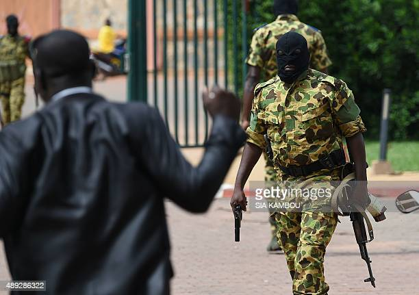 An armed soldier of the Presidential Security Regiment patrols outside the Hotel Liaco as they try to disperse members of Burkinabe organisation Le...