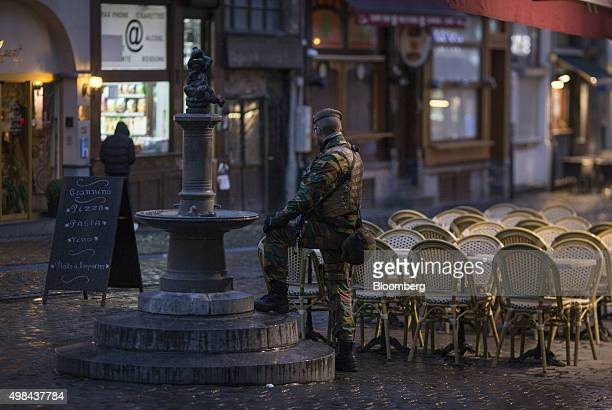 An armed soldier stands beside empty restaurant tables and seating near Grand Place square in Brussels Belgium on Sunday Nov 22 2015 The search for a...