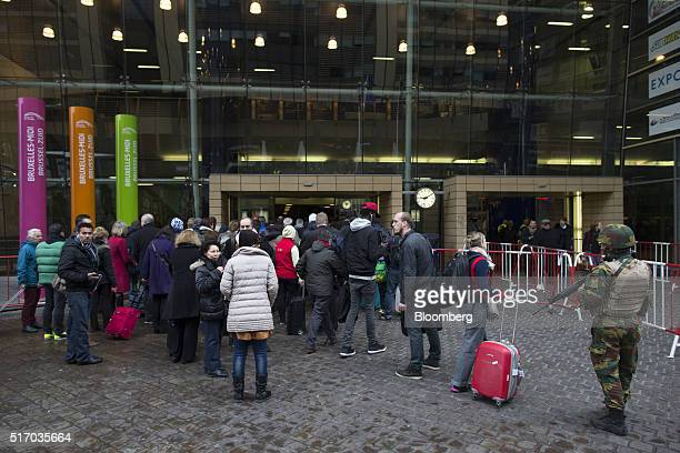 An armed soldier stands guard as travelers queue to enter Brussels Midi railway station in Brussels Belgium on Wednesday March 23 2016 Belgian...