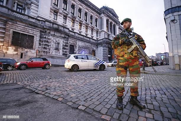 An armed soldier stands next to a police car as heavy security measures were deployed all around the Palace of Justice in Brussels on January 21 2015...