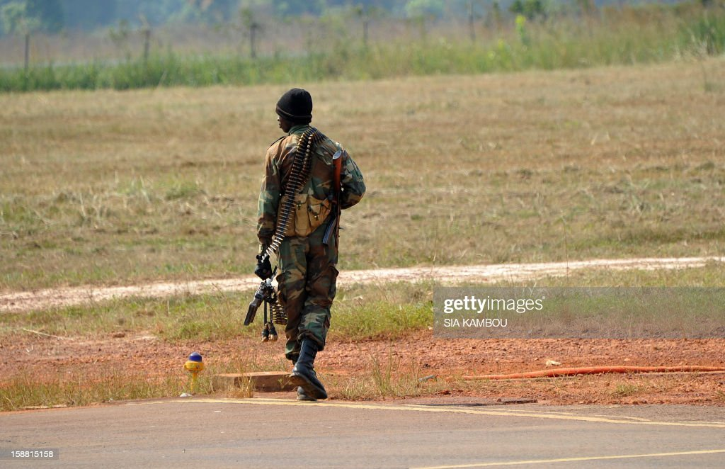 An armed soldier walks at the airport in Bangui as the President of the Central African Republic greets the current president of the African Union and President of Benin, on December 30, 2012. Rebels in the Central African Republic who have advanced towards the capital Bangui warned they could enter the city even as the head of the African Union prepared to launch peace negotiations. Central African President Francois Bozize also stated today he was open to a national unity government after talks with rebel leaders and that he would not run for president in 2016. AFP PHOTO/ SIA KAMBOU
