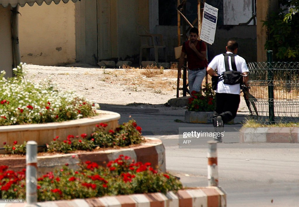 An armed supporter of radical Sunni Muslim sheikh, Ahmad al-Assir, who opposes the powerful Shiite movement Hezbollah runs across the street during clashes with Lebanese army personnel on June 23, 2013 in the village of Abra, on the outskirts of the southern Lebanese city of Sidon. The fighting erupted when Assir supporters surrounded an army checkpoint in Abra, where a vehicle transporting other supporters of the Sunni cleric had been stopped, a security source told AFP. AFP PHOTO / MAHMOUD ZAYYAT