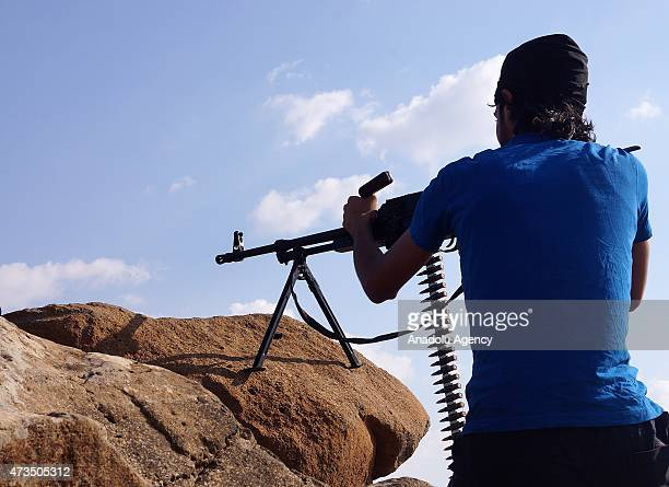 An armed Syrian opponent takes his position at a ditch in the Nahta region of Daraa Syria on May 15 2015 as they attack regime forces