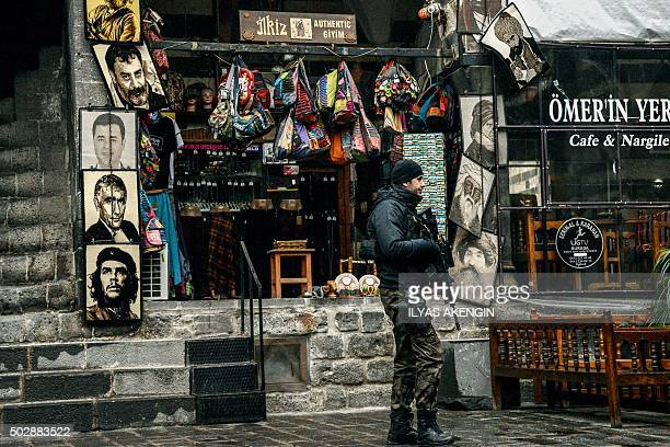 TOPSHOT An armed Turkish police officer patrols past a store in the historical Sur district on December 30 2015 in the mainly Kurdish city of...