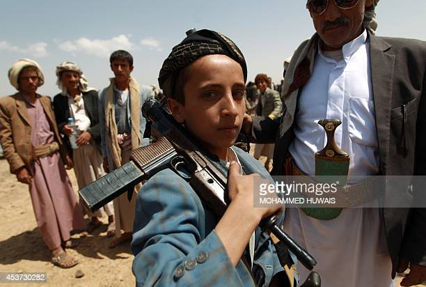 An Armed Yemeni boy loyal to the Shiite Huthi movement poses for a picture during a tribal gathering against alQaeda militants in the Bani alHarith...