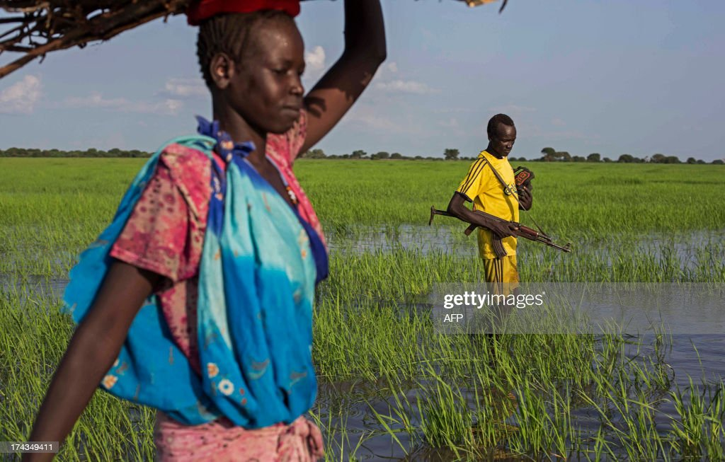 An armed youth walks through a river as he comes back home in the Yuai village, Uror county, Jonglei state in South Sudan on July 24, 2013 after fighting against the rebel group of Yau Yau in Pibor county, South Sudan. Over 100,000 South Sudanese civilians are cut off from aid in the eastern state of Jonglei amid fierce fighting between rival ethnic groups, aid agencies and the United Nations warned on July 17. AFP PHOTO / CAMILLE LEPAGE