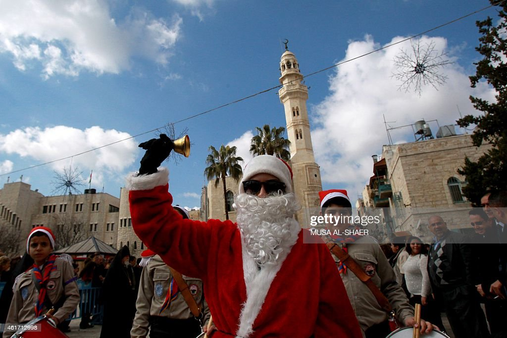 An Armenian girl dressed as Santa Claus takes part in a parade at Manger Square outside the Church of the Nativity during the Armenian Christmas...