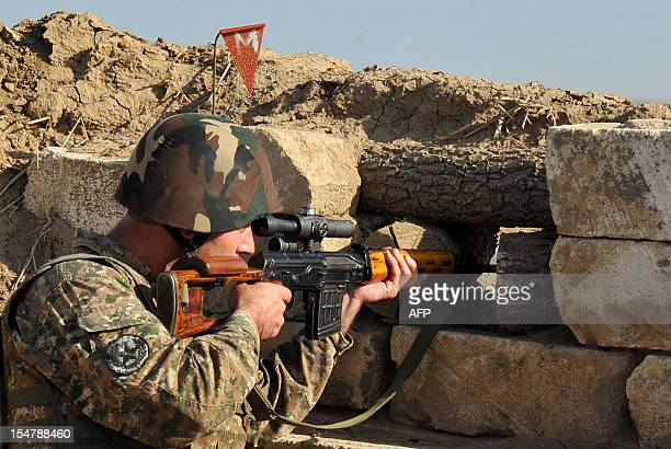 An Armenian soldier of the selfproclaimed republic of NagornoKarabagh aims his sniper rifle at the frontline on the border with Azerbaijan on October...