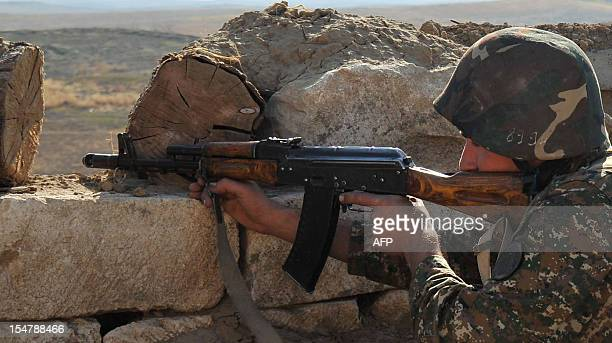 An Armenian soldier of the selfproclaimed republic of NagornoKarabagh aims his assault rifle at the frontline on the border with Azerbaijan on...