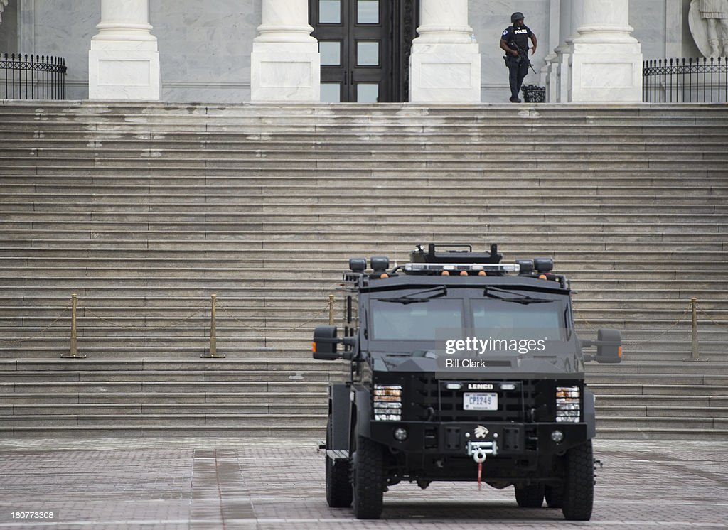An armored police vehicle and an officer in body armor stand guard in the East Plaza of the Capitol as US Capitol Police conduct enhanced security...
