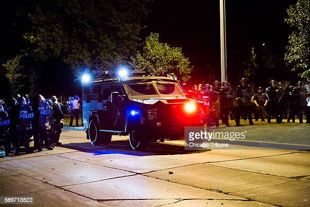 An armored vehicle positions itself to protect law enforcement after rocks and bottles were thrown by rioters during protests following a fatal...