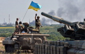 An armoured personnel carrier flying Ukraine's flag and a Ukrainian tank from a convoy of the Ukrainian forces drive towards the eastern Ukrainian...