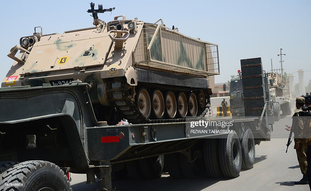 An armoured personnel carrier is transported as Pakistan soldiers set off for their deployment points from the Malir Cantonment ahead of parliamentary elections in Karachi on May 3, 2013. Pakistan will deploy more than 600,000 security personnel during next week's general election to guard against Taliban attacks that have marred campaigning. The May 11 polls will mark the first time that a civilian government has completed a full five-year term and handed over to an elected successor, in a country ruled by the military for half its 66-year history. AFP PHOTO/RIZWAN TABASSUM