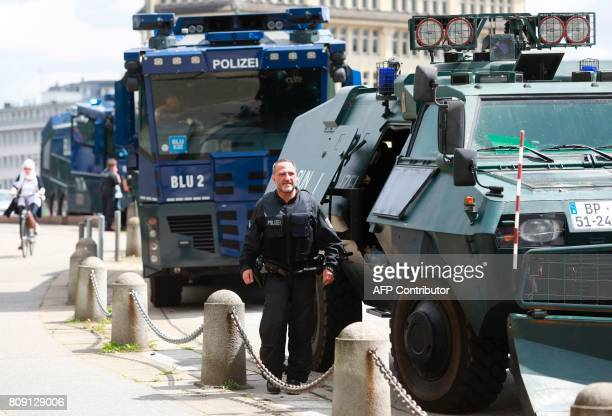 An armoured police vehicle and water cannon trucks are stationed against riots near the main station on July 5 2017 in Hamburg northern Germany where...