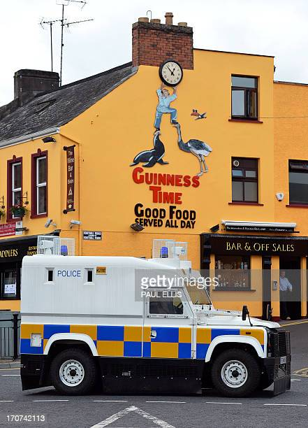 An armoured police vehicle deives past a pub advertsing Guinness in Enniskillen in Northern Ireland on June 17 near the Lough Erne resort where the...