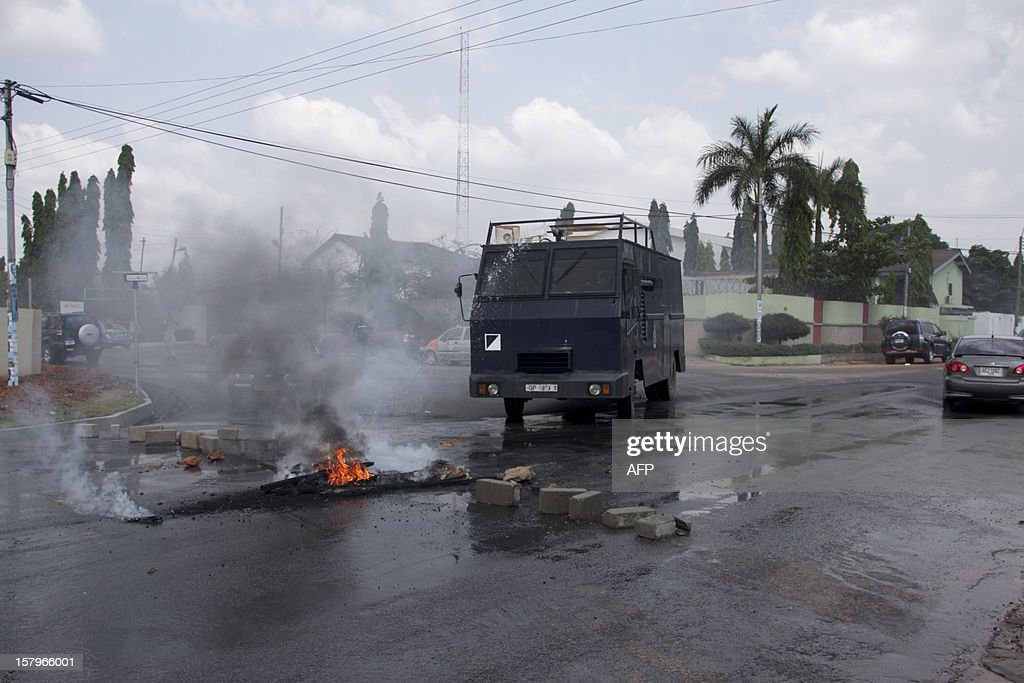 An armoured police vehicle douses burning rubbish lit by protesters angry over alleged vote-rigging on December 8, 2012 in Accra.Ghanaian authorities fired tear gas on Saturday to disperse a crowd of more than 100 people in the capital Accra who were angry over rumours of rigging in the country's elections. AFP PHOTO