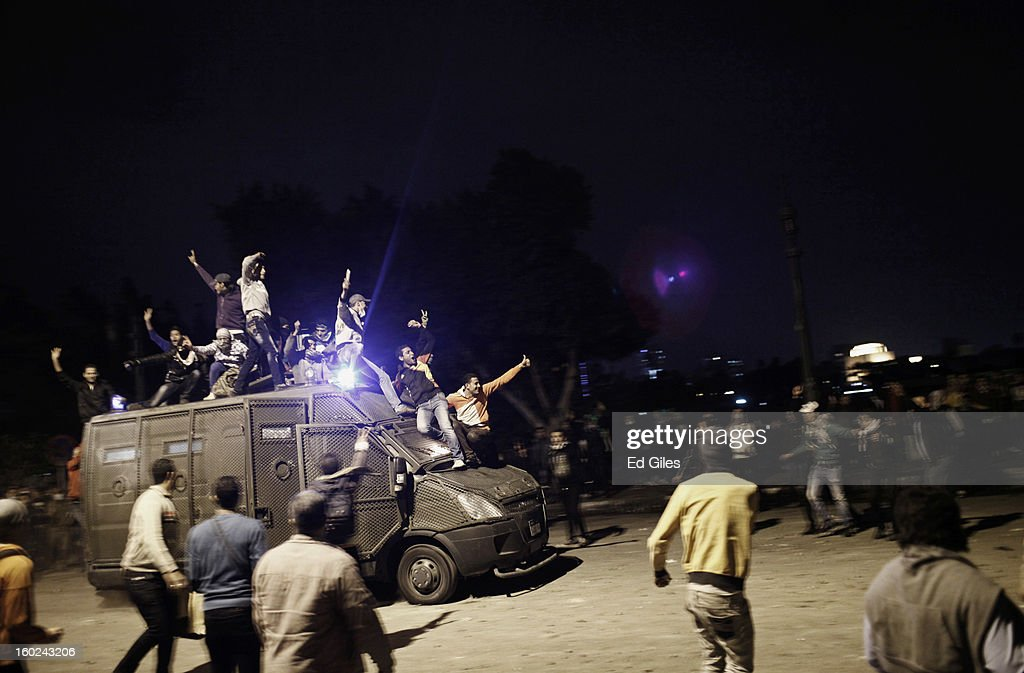 An armoured vehicle belonging to the Egyptian riot police, or Central Security Forces, is driven along a road with Egyptian protesters on top after being stolen during clashes between protesters and Egyptian riot police near Tahrir Square on January 28, 2013 in Cairo, Egypt. Violent protests continued across Egypt three days after the second anniversary of the Egyptian Revolution that overthrew former President Hosni Mubarak and two days after 21 men were sentenced to death in connection with the deaths of 74 football fans during riots at Port Said stadium one year ago.
