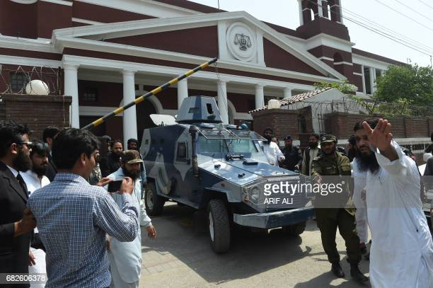 An armoured vehicle carries the head of Islamic group of JamaatudDawa Hafiz Saeed as he leaves a court in Lahore on May 13 after the expiry of his...
