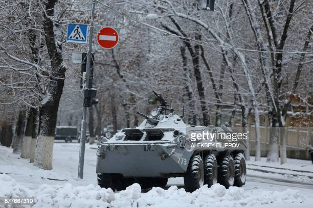 An armoured vehicle is seen next to government buildings in eastern Ukraine's rebelheld Lugansk on November 23 2017 The patrols began after an...