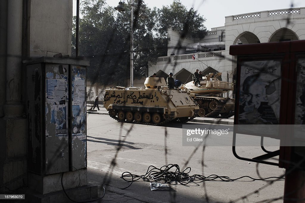 An armoured vehicle of the Egyptian Republican Guard is parked by the outer walls of Egypt's Presidential Palace, marked by anti-Morsi graffiti during a demonstration against Egyptian President Mohammed Morsi the previous night, on December 8 in Cairo, Egypt. Anti-Morsi protesters continue to demonstrate across Egypt against the country's draft constitution, rushed through parliament in an overnight session on November 29. The country's new draft constitution, passed by a constitutional assembly dominated by Islamists, will go to a referendum on December 15. (Photo by Ed Giles/Getty Images).
