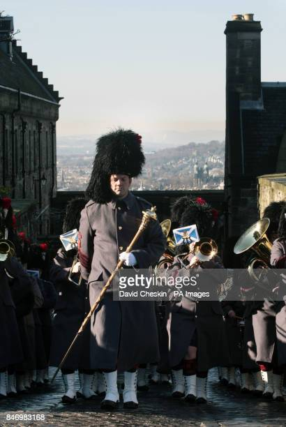 An army band march as gunners from 105 Regiment Royal Artillery prepare to fire a 21 gun Royal Salute from Edinburgh Castle to celebrate the 60th...