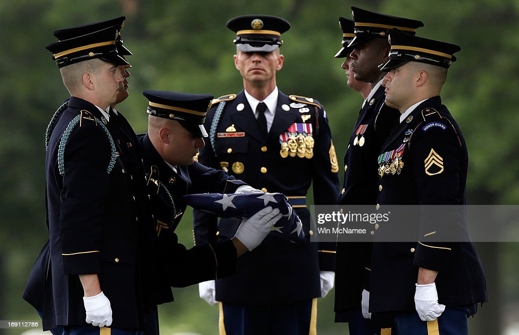 An Army burial team folds an American flag during a burial service for Sergeant First Class James F. Grissom at Arlington National Cemetery May 20, 2013 in Arlington, Virginia. Grissom, from Hayward, California, died from wounds suffered in combat in Paktika province, Afghanistan.
