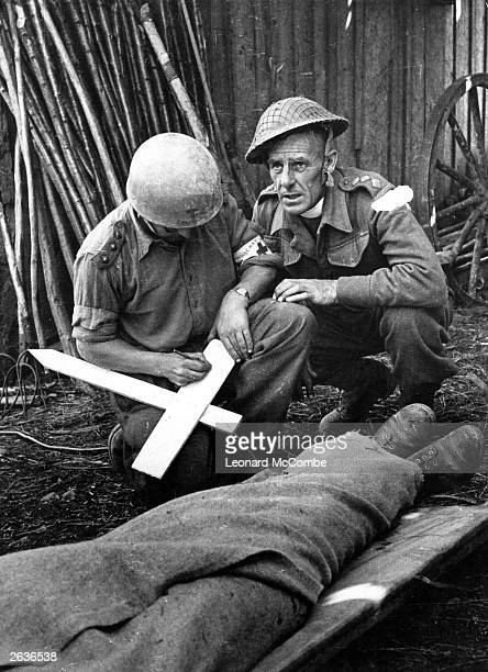 An army chaplain and and another man in a clerical collar and captain's uniform give a hasty makeshift funeral to a casualty behind the Normandy...