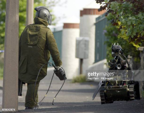 An Army explosives expert manoeuvres a remote controlled robot after a Sinn Fein member found two pipe bombs under his car and at the side of his...