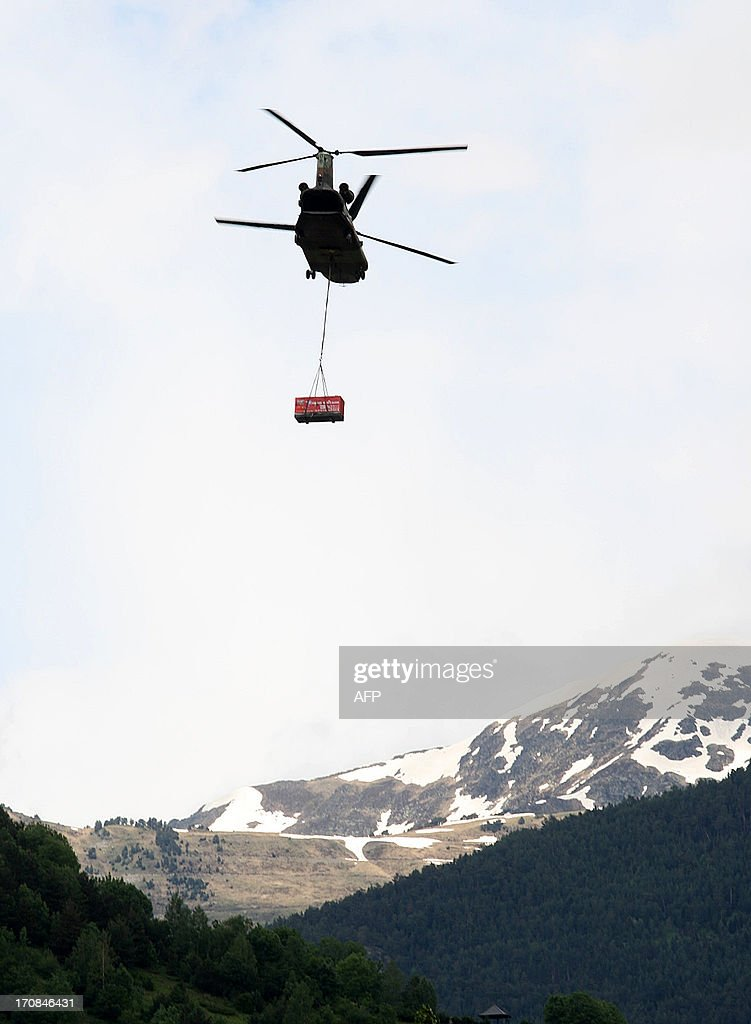 An army helicopter transports an electric generator in Vielha, northeastern Spain, on June 19, 2013. Around 350 people were evacuated due to floods in the area. AFP PHOTO / QUIQUE GARCIA