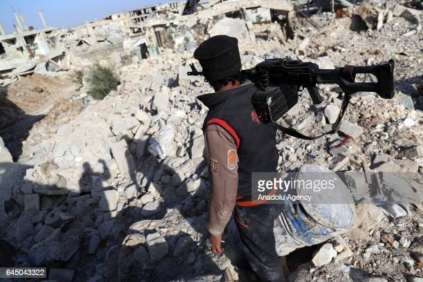 An army member with a machine gun walks along the wreckages caused by Assad regime forces' violations of ceasefire which ruined the Mensheyya...