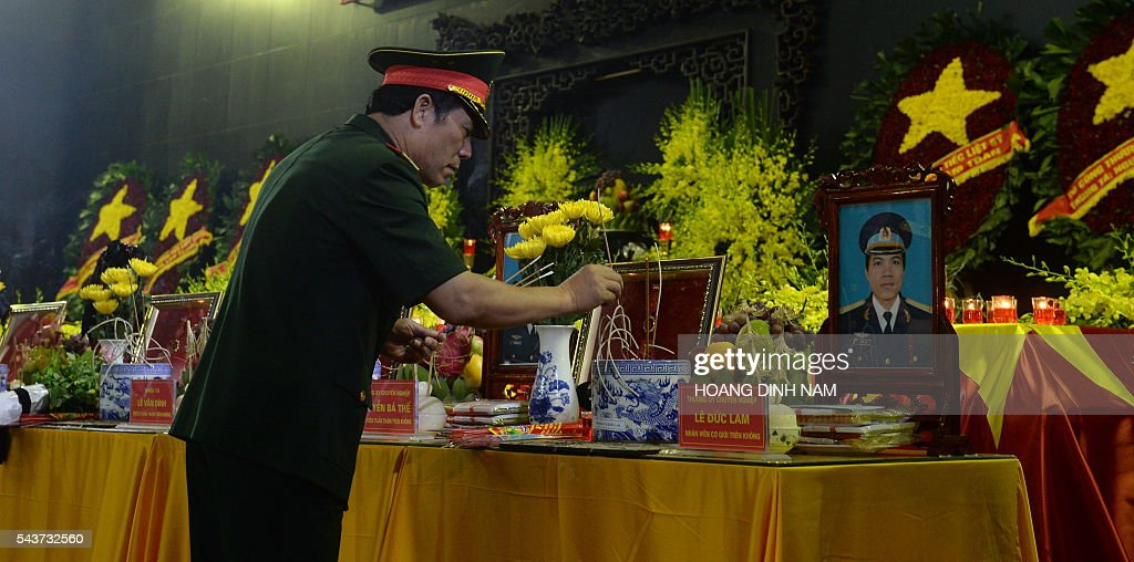 An army officer places incense sticks as he pays tribute to the victims of a rescue aircraft that crashed on June 16, 2016 over the South China Sea during a search mission for a Vietnamese Airforce Sukhoi SU-30MK2 that went missing two days earlier, during an official funeral ceremony in Hanoi on June 30, 2016. / AFP / HOANG