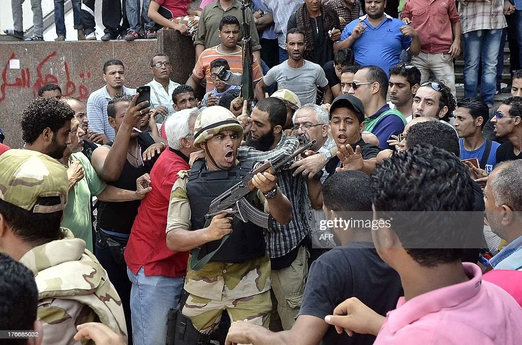 An army officer tries to control the crowd as he escorts an Islamist man out of Cairo's AlFath mosque where Islamist supporters of ousted president...