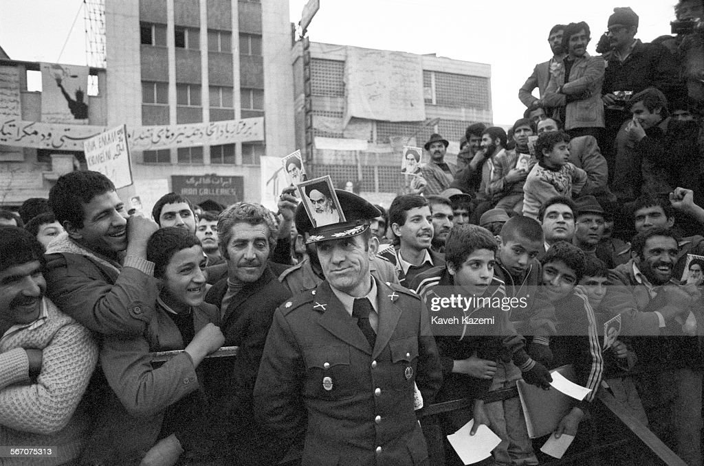 An army officer with a photo of Ayatollah Khomeini on his hat stands among people demonstrating outside the American Embassy which is occupied by...