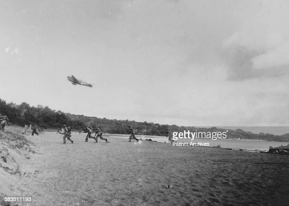 An Army P40 gives close air support on the beach to United States troops and soldiers attacking Japanese forces at Rendova Island of the Solomon...