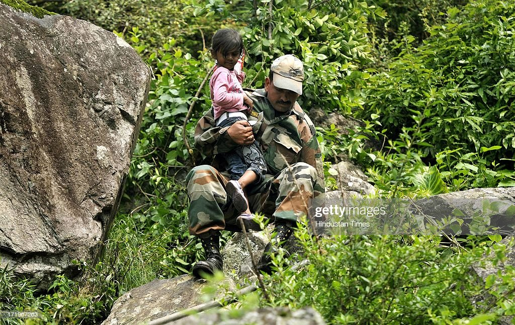 An Army personnel helping a 4yr Khanak Saxena to cross a rocky stretch at Govind Ghat on June 30 2013 in Uttarakhand, India. People who are stranded at Badrinath got agitated as their token for helicopter rescue are being mismanaged and henceforth opted to walk down through mountains.