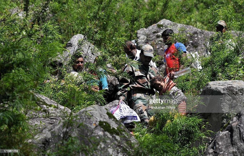 An Army personnel helping a little child to cross a rocky stretch at Govind Ghat on June 30 2013 in Uttarakhand, India. People who are stranded at Badrinath got agitated as their token for helicopter rescue are being mismanaged and henceforth opted to walk down through mountains.