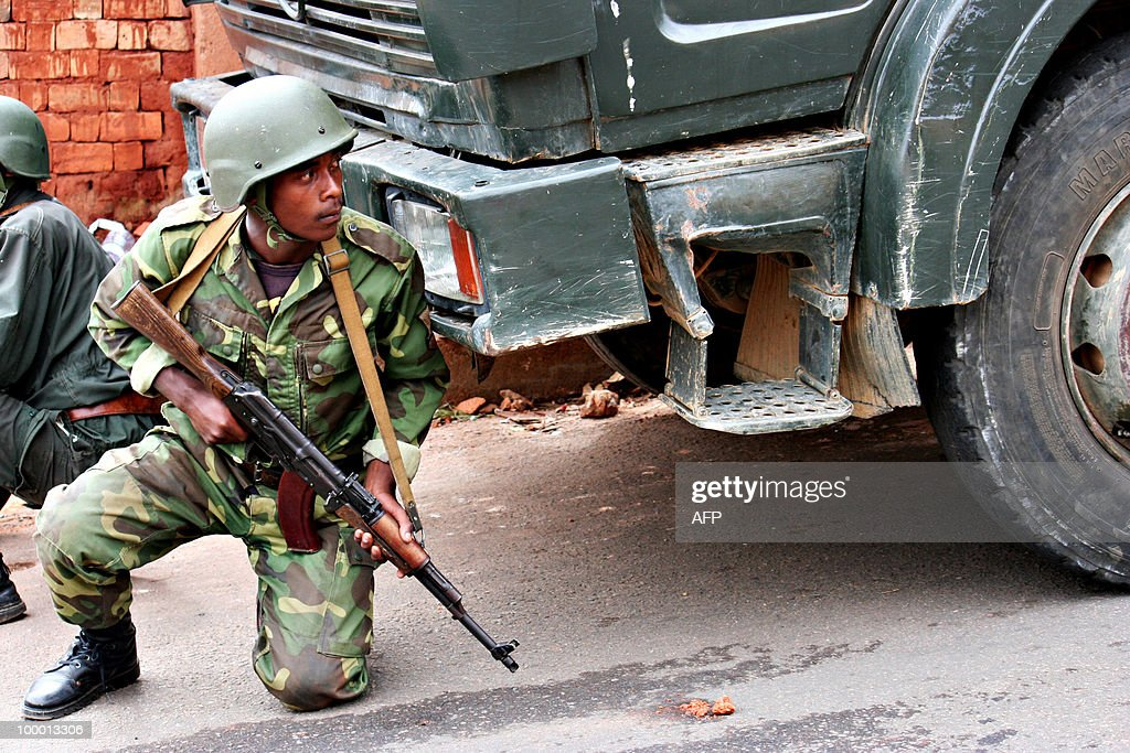 An army soldier takes cover behind a military truck during a shoot out between rival Madagascan security forces in the streets of Madagascar's capital, Antananarivo on May 20, 2010. The shooting broke out when army and gendarmerie units confronted members of the gendarmerie's elite intervention unit (FIGN) who began a protest against their superiors on May 19. It was not immediately clear whether there was any political dimension to the clash, which erupted as political players on the Indian Ocean island nation struggled to find a way out of a crisis sparked by a March 2009 coup.