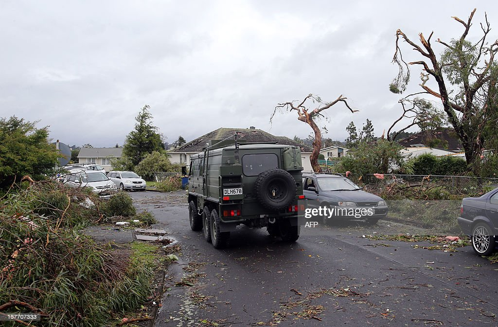 An army truck drives down on a road amongst debris in Hobsonville, Auckland on December 6, 2012 after packed wind gusts of up to 110 kilometres (70 miles) per hour, struck suburban Hobsonville in the afternoon. A freak storm described by police as a tornado hit New Zealand's largest city Auckland on December 6 causing 'utter devastation', with three people reportedly killed in ferocious winds. AFP PHOTO / Michael Bradley