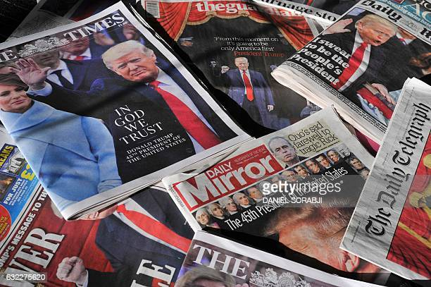 An arrangement of daily newspapers from Satutrday January 21 showing front page stories reporting US President Donald Trump's inauguration in...