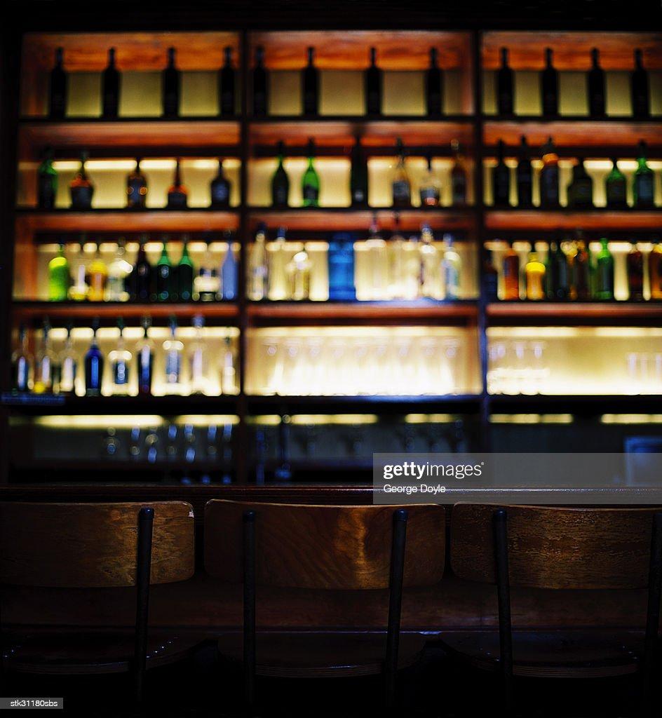an array of bottles kept in shelves at a bar : Stock Photo