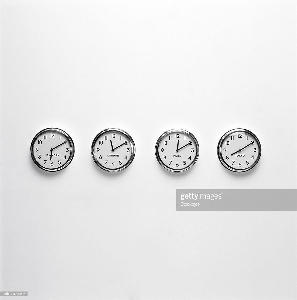 an array of wall clocks displaying world time