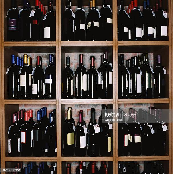 an array of wine bottles kept on display in shelves