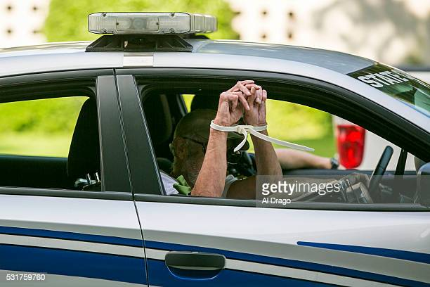 STATES MAY 16 An arrested protestor is taken away in a police car after failing to disperse from the North Carolina state legislative building as...