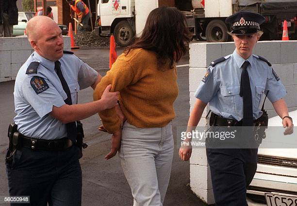 An arrested woman is led away by police outside the Otahuhu District Court after scuffles broke out in the courthouse between the deceased childs...