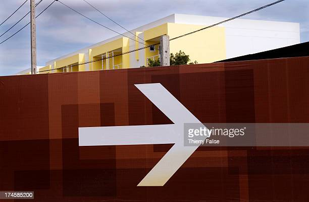 An arrow painted on a wall shows the direction to the entrance of a new real estate project in Bangkok
