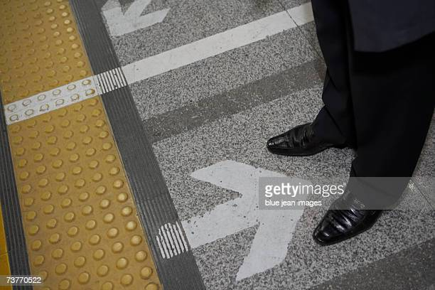 An arrow pointing towards a business man's feet standing on a subway platform